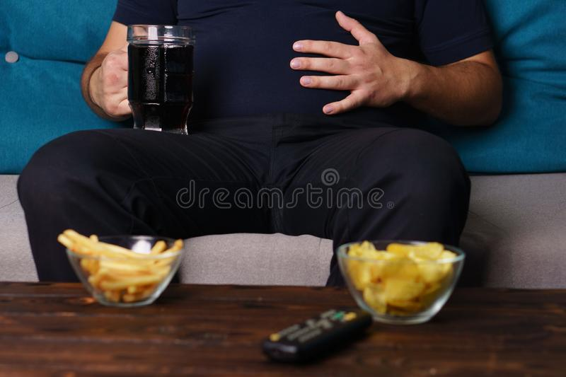 Overeating, sedentary lifestyle, bad habits. Food addiction, eating disorders. fat overweight man sitting on the sofa with junk food and tv remote. depression royalty free stock photo