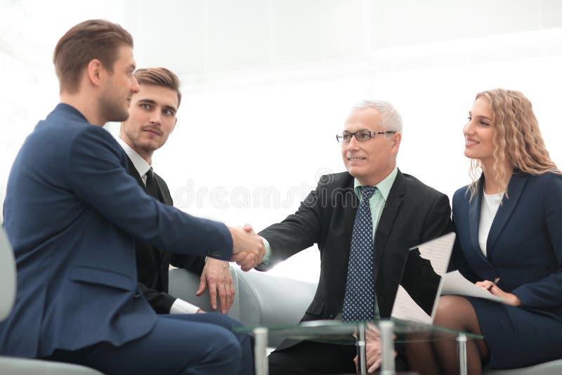 Overeenkomst besluiten en partners die dient de aanwezigheid van teamleden de schudden in stock afbeelding