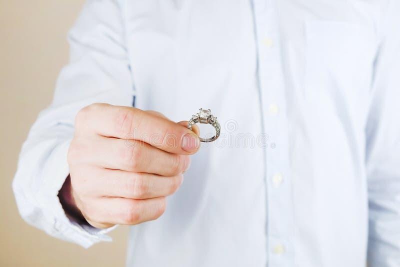 Overeenkomst/huwelijks/huwelijksvoorstelscène Sluit omhoog van de mens die de dure gouden ring van de platinadiamant overhandigen stock fotografie