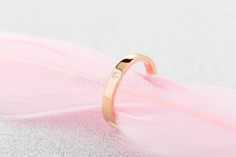 Overeenkomsten gouden ring met één diamant op roze veer stock foto