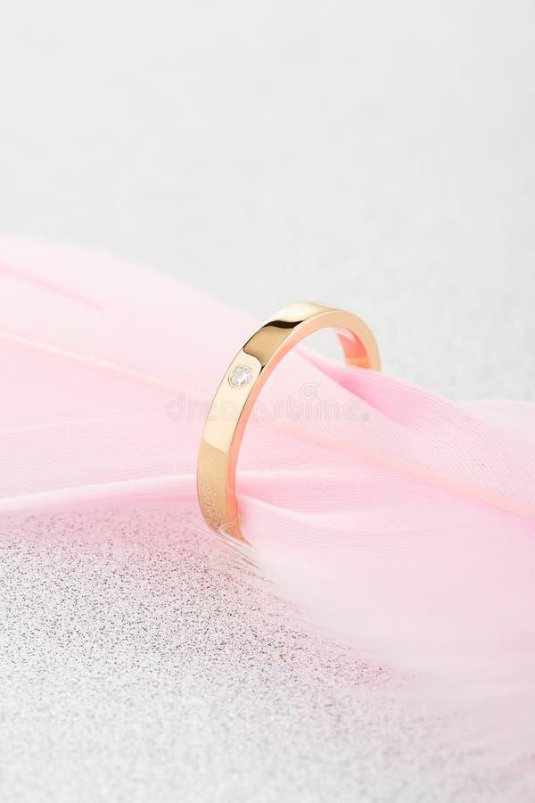 Overeenkomsten gouden ring met ??n diamant op roze veer stock foto's