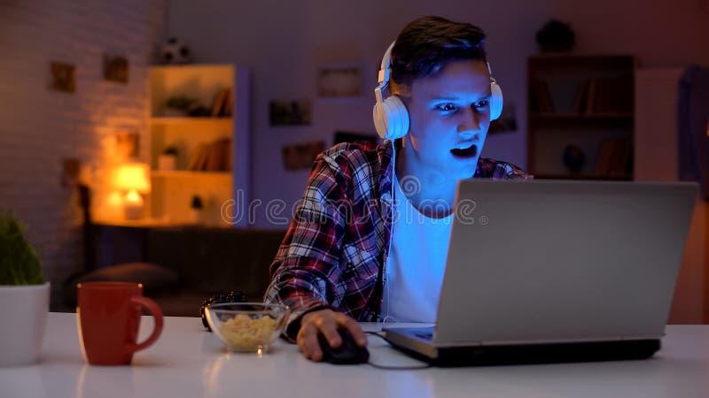 Overemotional jugendlich spielendes Computerspiel auf Laptop und essen Imbissen, Sucht stockfotografie