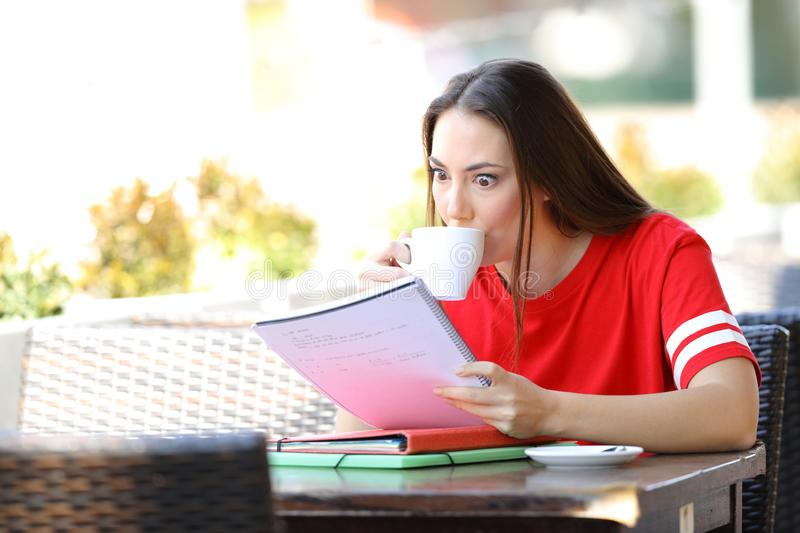 Overexcited student studying drinking coffee stock photography