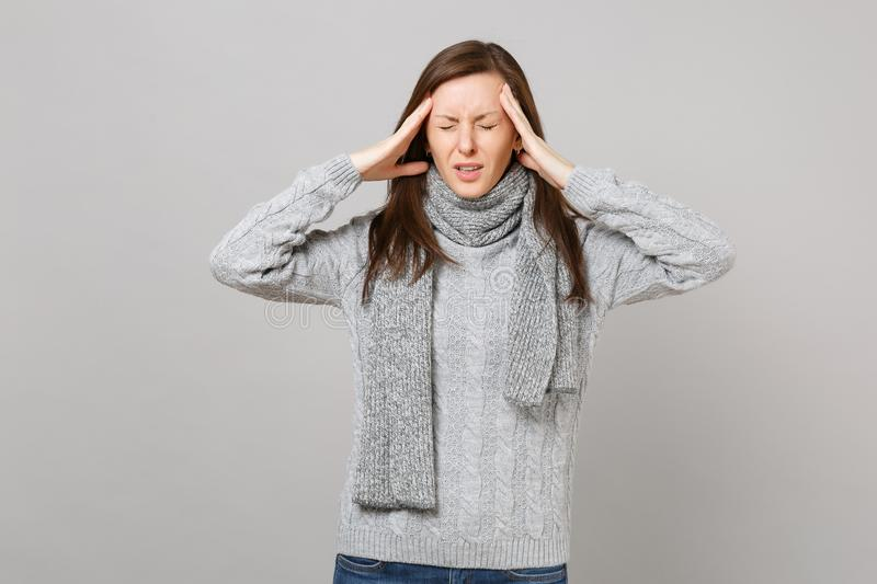 Overexhausted young woman in gray sweater, scarf with closed eyes putting hands on head, having headache isolated on royalty free stock image