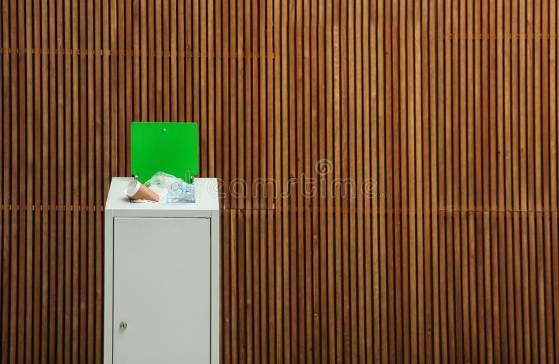 Overfilled trash bin near wooden wall, space for text. Recycling concept stock photography
