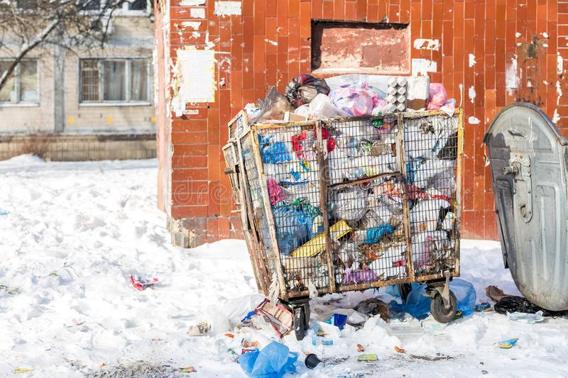 Overfilled waste container on city street. Garbage bin made of metal cage for plastic dump. Environment pollution . Plastic goods stock photos