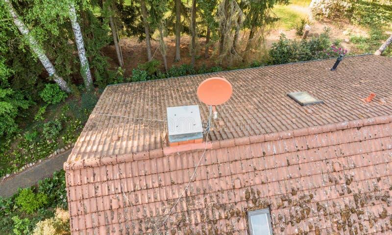 Overflight do telhado de uma casa destacada para verificar a condição da antena satélite para ver se há a recepção da televisão e foto de stock royalty free
