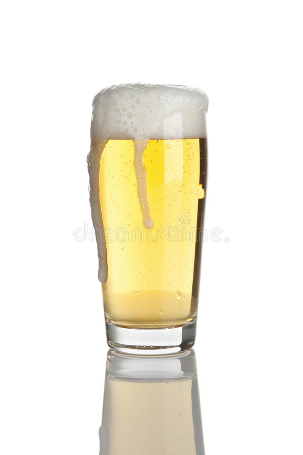 Overflowing glass of fresh lager beer stock photo