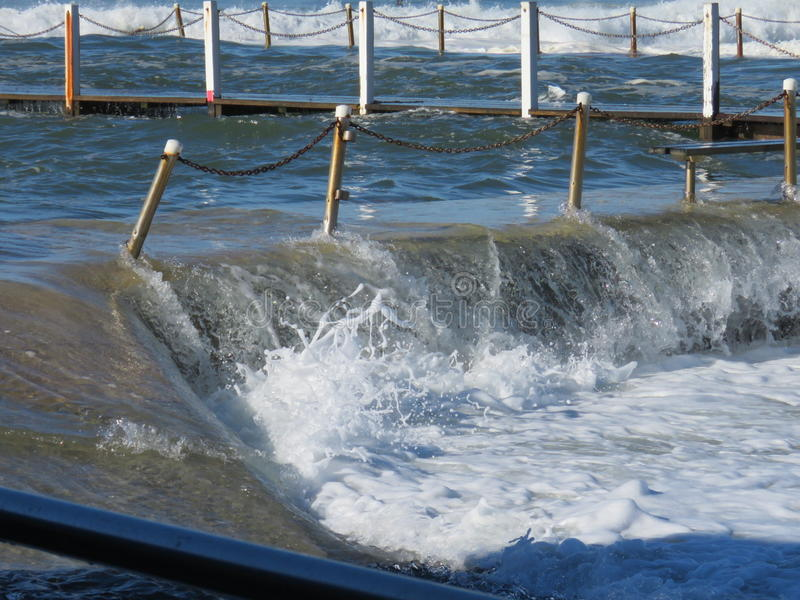 Overflowing ocean pool. After storms and high tides, the Narrabeen ocean pool spills water lie an overflowing dam. Boardwalks are awash and closed for safety royalty free stock images