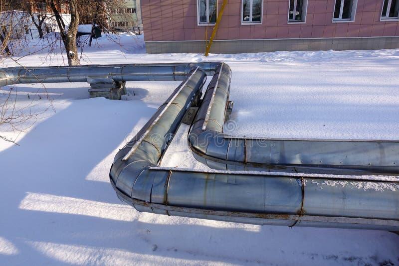 Overground热导管 在地面,加热的城市举办的热上的管道 冬天 雪 免版税库存照片