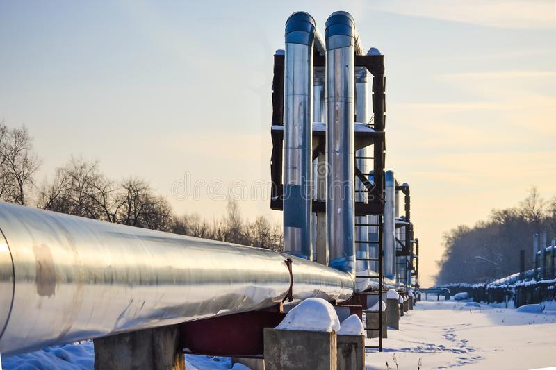 Overground heat pipes. Pipeline above ground, conducting heat for heating the city. Winter. Snow. Overground heat pipes. Pipeline above ground, conducting heat royalty free stock photography