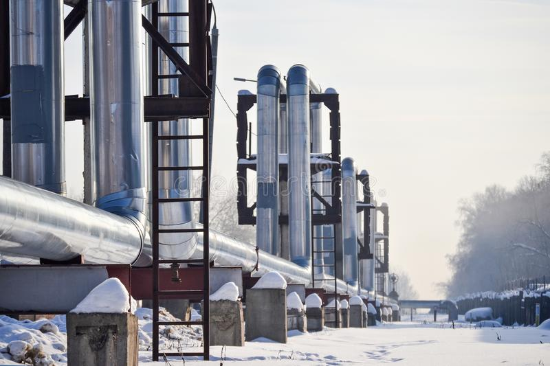 Overground heat pipes. Pipeline above ground, conducting heat for heating the city. Winter. Snow. stock photos