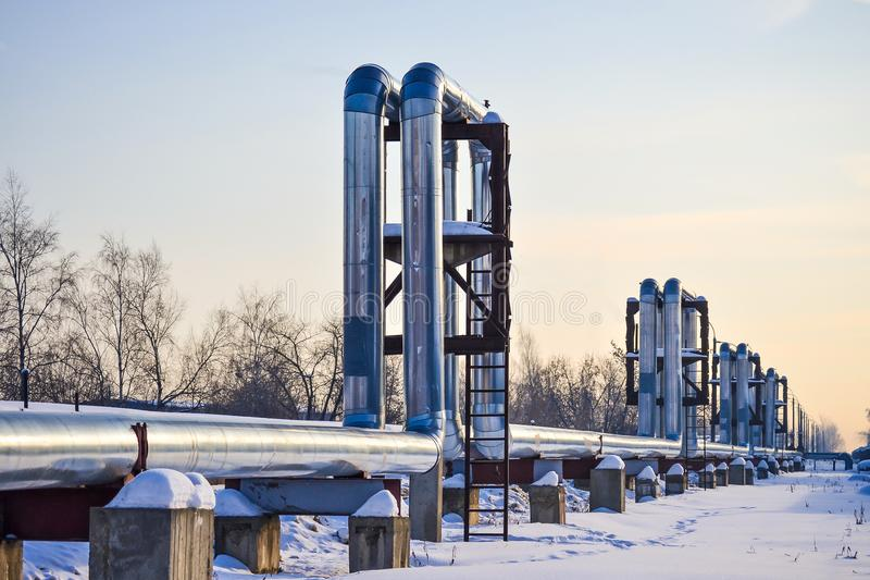 Overground heat pipes. Pipeline above ground, conducting heat for heating the city. Winter. Snow. royalty free stock image