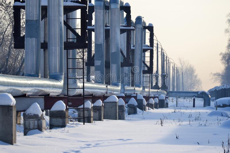 Overground heat pipes. Pipeline above ground, conducting heat for heating the city. Winter. Snow.  stock images