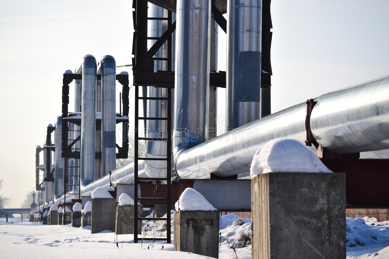 Overground heat pipes. Pipeline above ground, conducting heat for heating the city. Winter. Snow stock photos