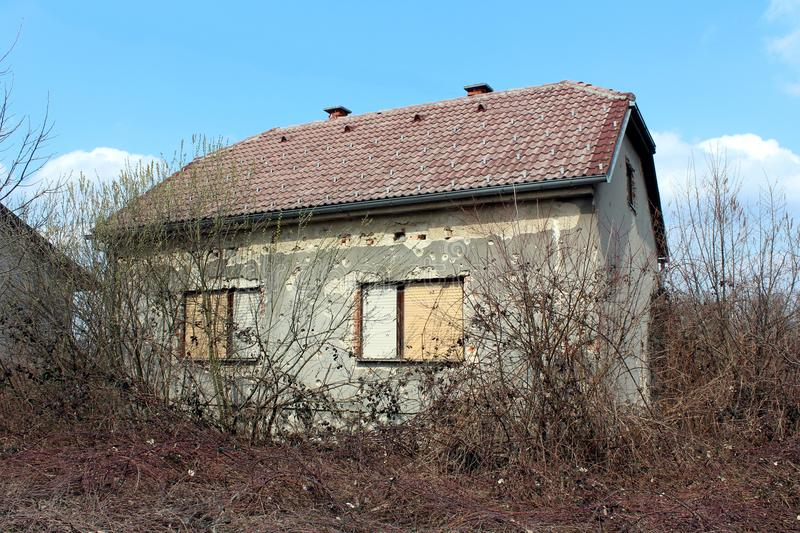 Overgrown suburban family house damaged by shrapnels during war. Small suburban family house damaged by shrapnels during war with dilapidated facade, visible royalty free stock photo