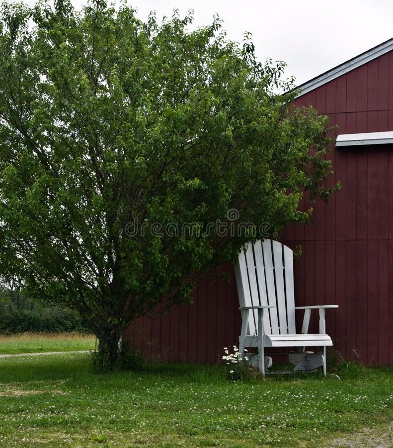 Free Overgrown, White Lawn Chair In Front Of Simple Red Barn Under Green Tree Royalty Free Stock Photography - 151686017