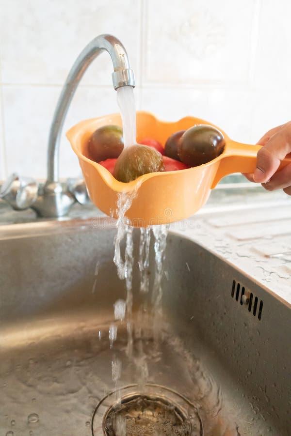 overhandig het houden van een vergiet met vers fruit en bessen en het wassen van het in de keuken met wateren stock foto