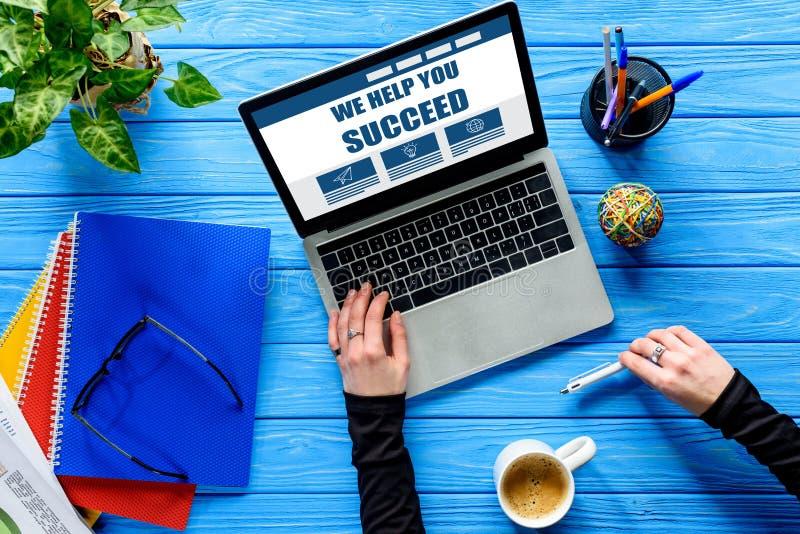 overhandig het typen op laptop toetsenbord op blauwe houten lijst met kantoorbehoeften en koffie, helpen wij u royalty-vrije stock afbeeldingen