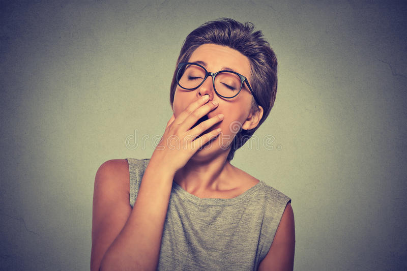 Overhandigt de Headshot slaperige jonge vrouw met open mond geeuw stock afbeeldingen