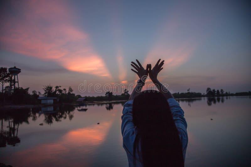 Overhandigt de silhouet Jonge vrouw sunsets stock foto's
