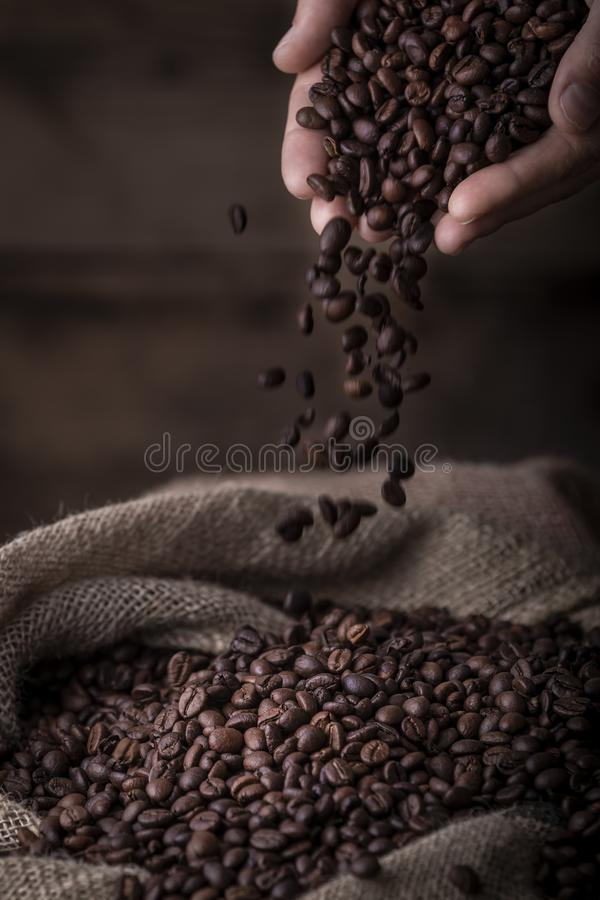 Overhandigt gietende koffiebonen aan zak stock foto's