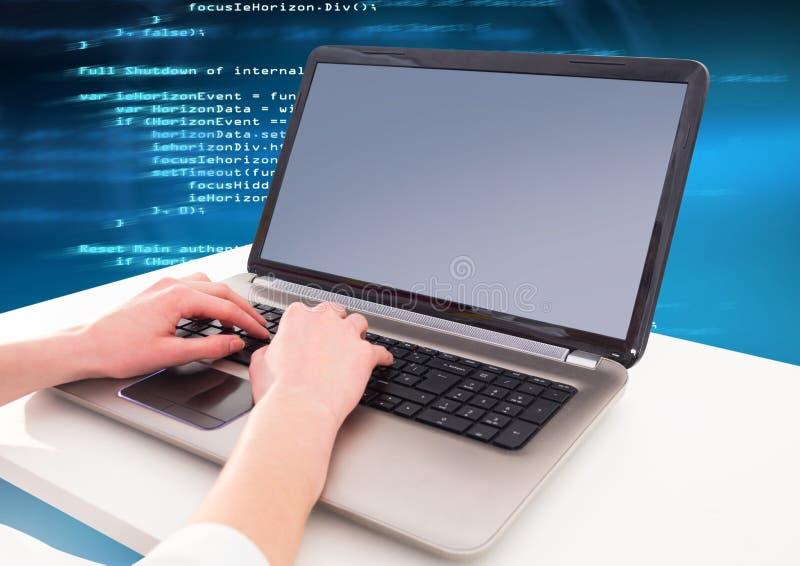 Overhandigt het typen codagetekst op laptop stock afbeelding