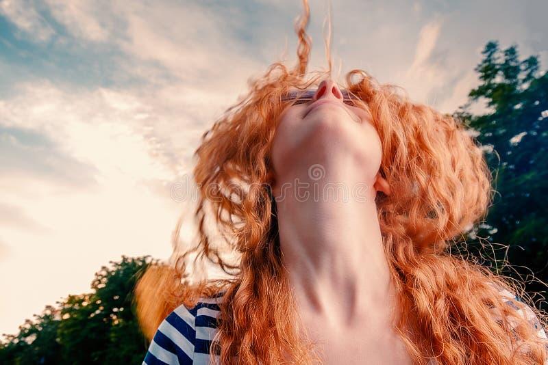 Overhappy rood haired meisje die met haar gezicht dansen die in de blauwe de zomerhemel kijken met wolken, copyspace royalty-vrije stock foto