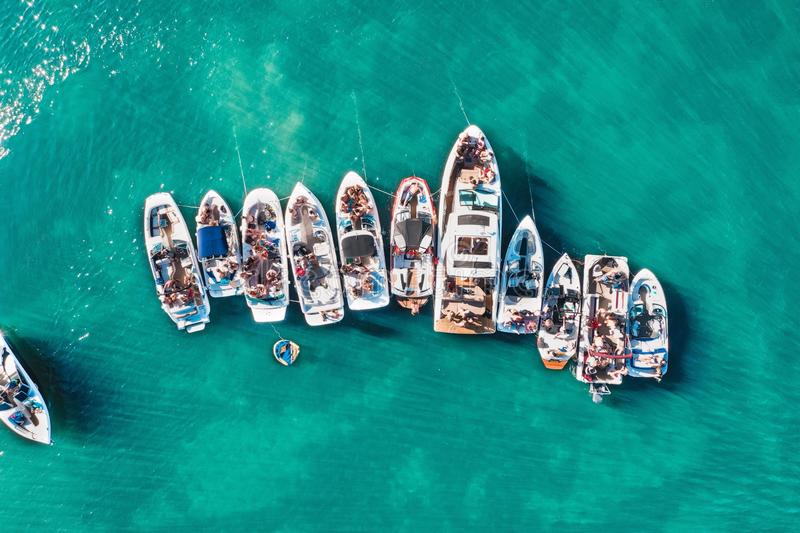 Overhead aerial drone shot of different sized boats docked close to each other near the pier royalty free stock photo