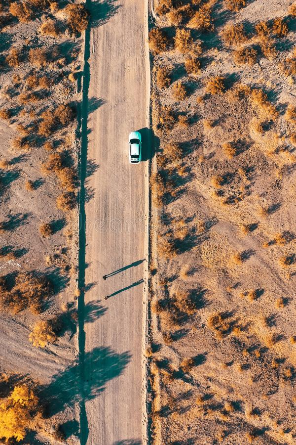 Overhead aerial drone shot of a narrow desert road with a car on the side of the road stock image