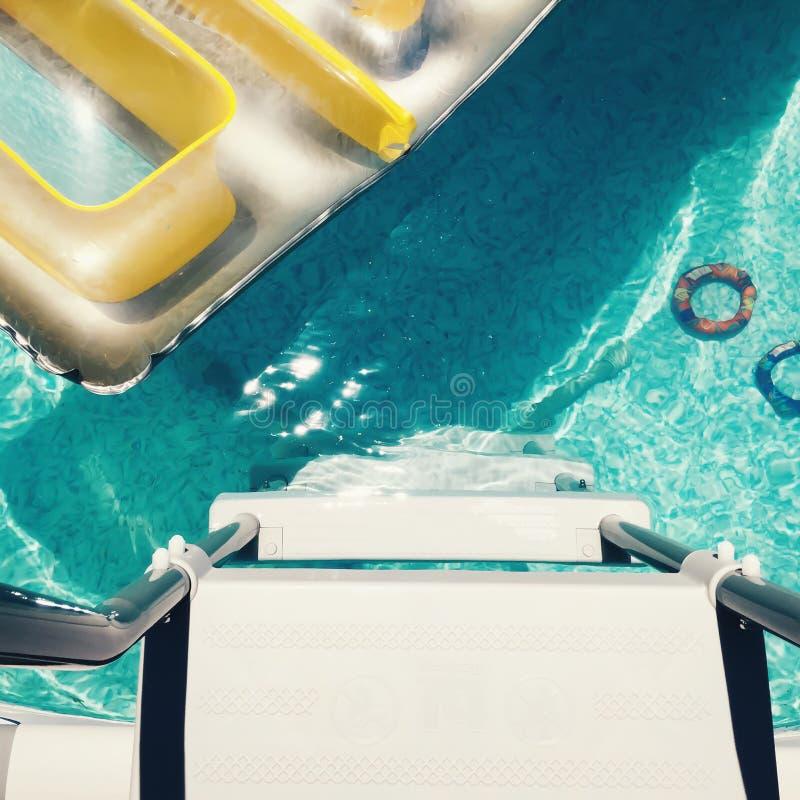 Overhead birdseye view of backyard swimming pool with toys. Overhead birdseye view of backyard swimming pool with lilo and toys royalty free stock images
