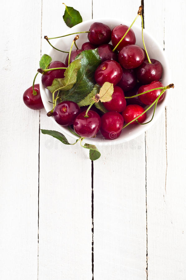 Overhead of bowl of red cherries in white dish stock image