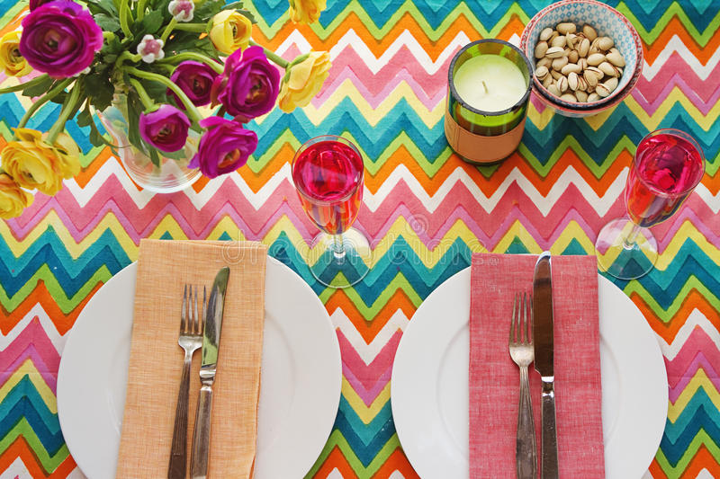 Overhead Bright colorful table setting with chevron tablecoth. Overhead Bright colorful table setting with multi colored chevron pattern tablecoth stock images