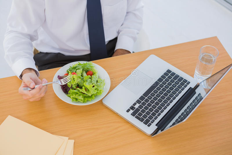 Overhead of a businessman eating a salad on his desk stock images