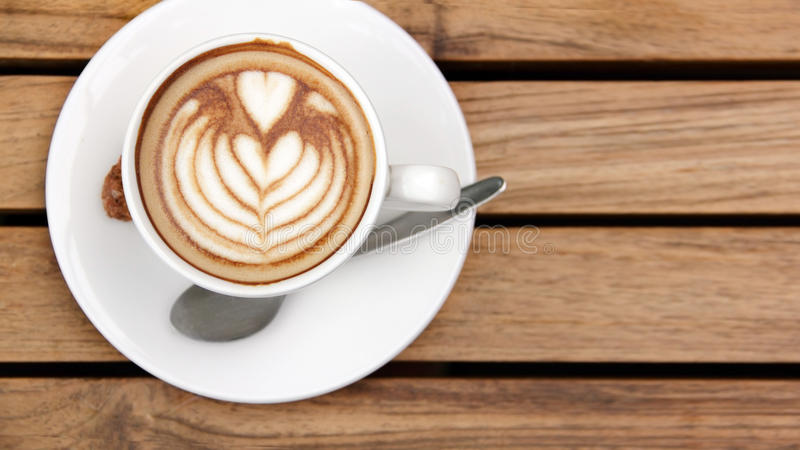 Overhead of cappuccino on wooden table. Overhead shot - a cup of cappuccino coffee laid on wooden table stock photo