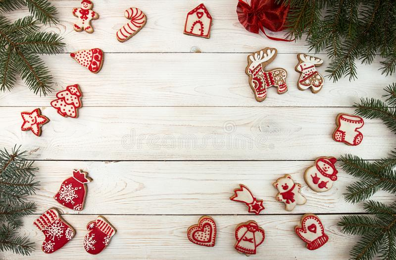 Overhead of Christmas New Year holiday background. Red gingerbread cookies and fir branch tree on white wooden table. Top view. royalty free stock images