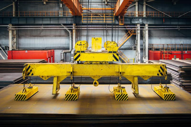 Overhead crane with magnetic grippers lifting steel sheets stock photo