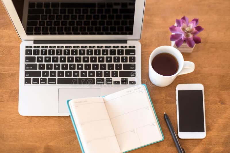 Overhead desk with calendar, laptop, coffee and smartphone royalty free stock photography