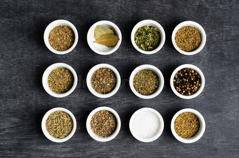 Overhead of Dried Herbs and Condiments in Bowls. Overhead shot of rows of dried herbs, salt and peppercorns in small bowls on a dusty, textured chalkboard stock photography