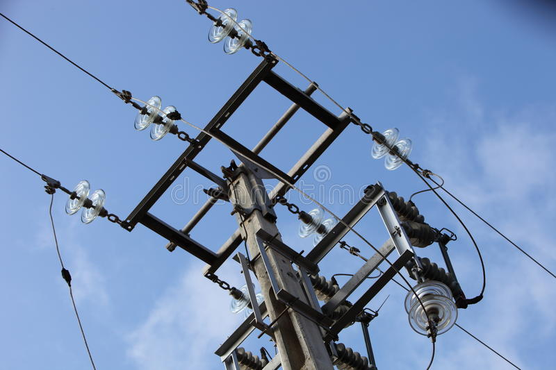 Overhead electricity pole against a blue sky royalty free stock images