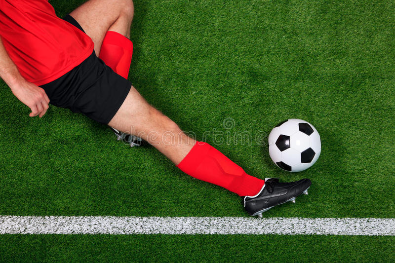 Overhead football player sliding. Overhead photo of a football or soccer player sliding in to save the ball going over the sideline royalty free stock images
