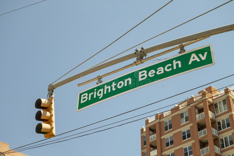 Overhead hanging Traffic light with green white street sign of Brighton beach ave stock image