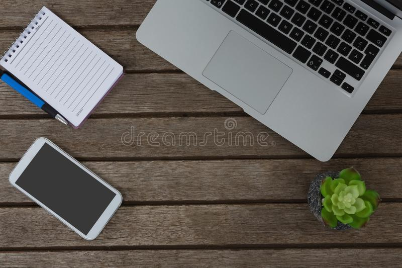 Laptop, pot plant, notepad, pen and mobile phone on wooden plank. Overhead of laptop, pot plant, notepad, pen and mobile phone on wooden plank royalty free stock images