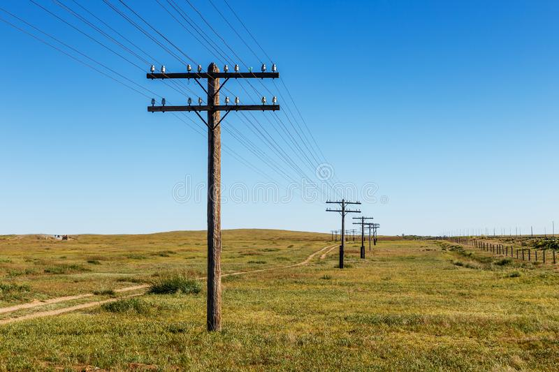 Overhead line on wooden supports in the Mongolian steppe royalty free stock photos