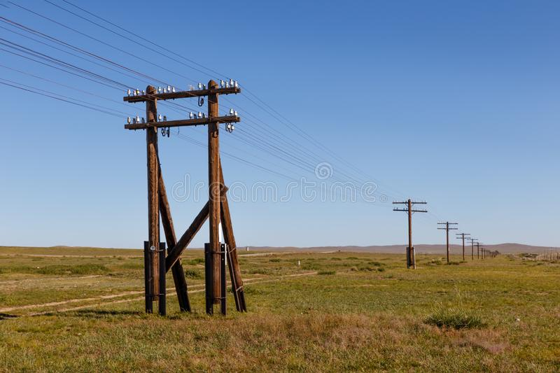 Overhead line on wooden supports in the Mongolian steppe. Mongolia stock images