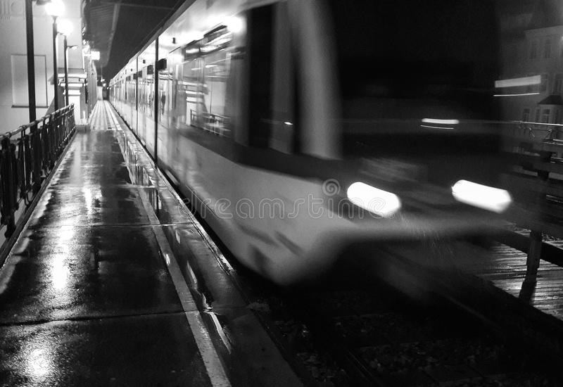 Metro Line Rush Hour Grunge. An overhead metro nightline rushes past the passenger embarcation platform during a storm stock image