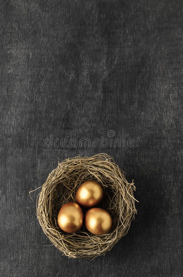 Overhead of Nest containing Three Gold Eggs on Chalkboard Background royalty free stock photos