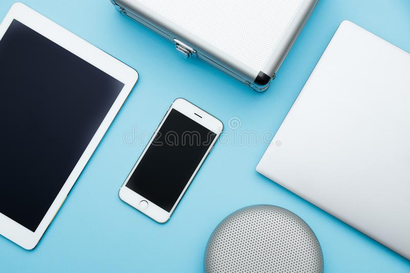 Overhead of office table with laptop, tablet pc, cellphone, speaker and bag. copy space blue flat lay stock photography