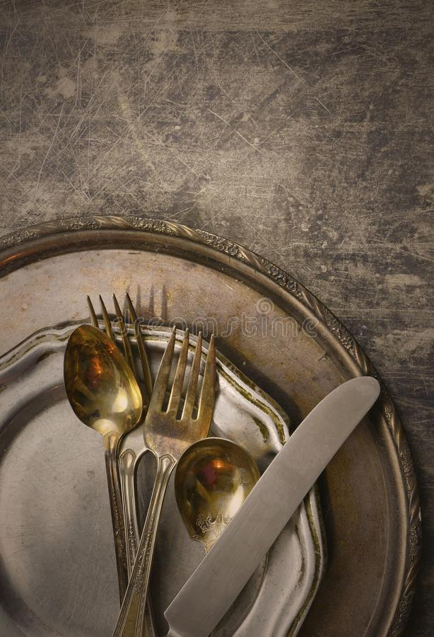 Overhead perspective of tarnished silver plated flat ware and platter with worn pewter dish on rustic steel background. Vintage fi. Lter added royalty free stock photo