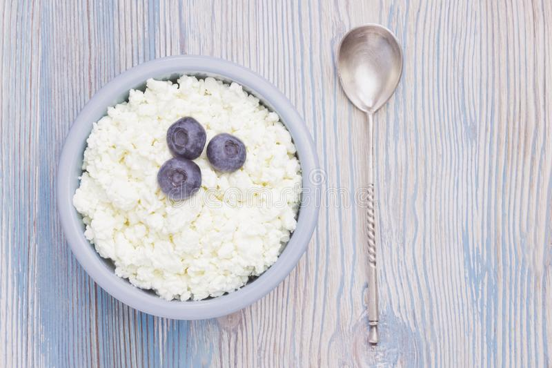 An overhead photo of fresh natural cottage cheese with blueberries and a silver spoon in a ceramic bowl on the wooden table. royalty free stock photos